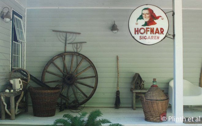 A Dutch cigar sign (Hofnar Sigaren translated as Jester) has been re-purposed as a cheeky ornament in the Vrijmoed's sun porch filled with garden antiques. The contrast between the rustic objects and the contemporary white chair on the right can hardly be more striking.