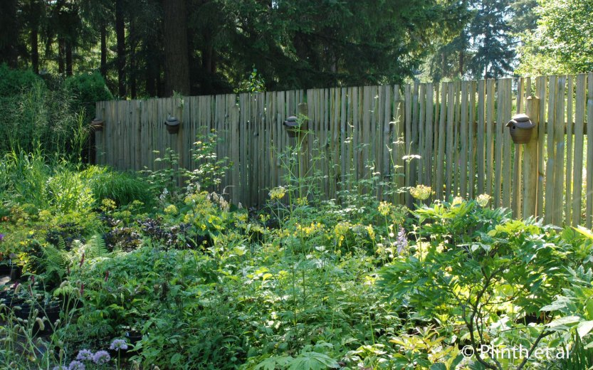 Ceramic bee houses are hung along the fence in the nursery area, affirming the Vrijmoed's pollinator-friendly philosophy.