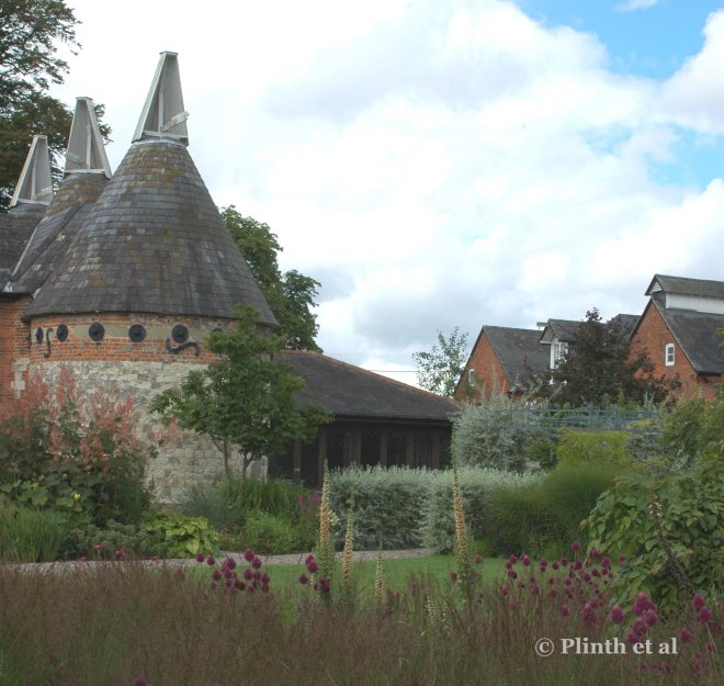 The trio of oasthouses, once used for drying hops, dominates the courtyard of the Oudolf garden. In the foreground the purple orbs of Allium sphaerocephalon and spires of Digitalis ferruginea bobble in Molinia grasses.