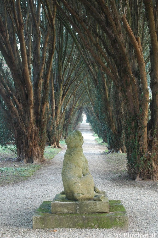As dark as the yews may be, they compel us to seek the light towards the end of the pathway (Yew Walk, Tregrehan, Cornwall, UK).