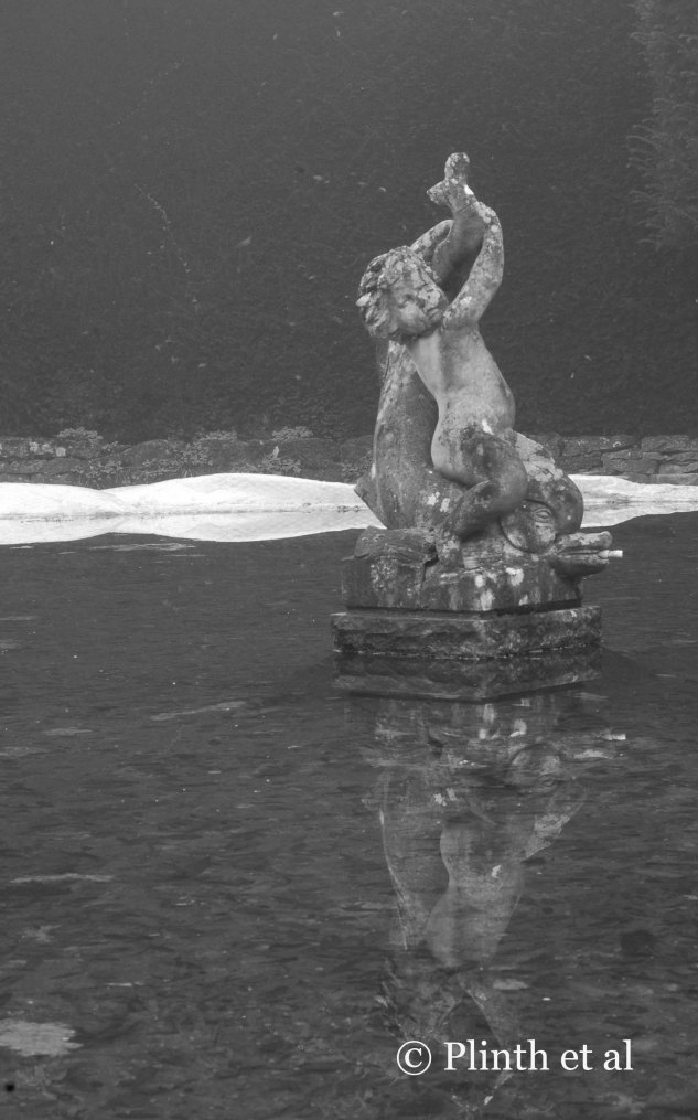 Reflected in the still waters of the Bathing Pool Fountain is the cherub and the dolphin centerpiece.