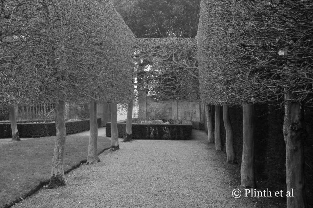 Denuded of their leaves, the pleached hornbeams become wiry edifices that play off texturally the solid boxwood and yew hedges, and the grass panel, walls, and gravel paths are tonally different from the clipped plants.