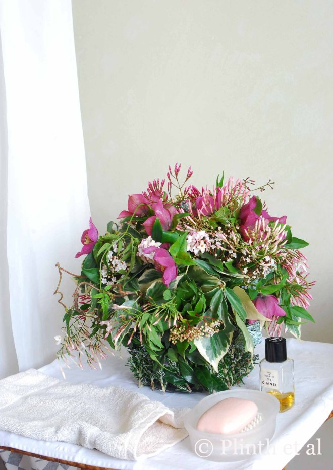 Placed in the airy bathroom, the floral arrangement is a potpourii of winter fragrances.