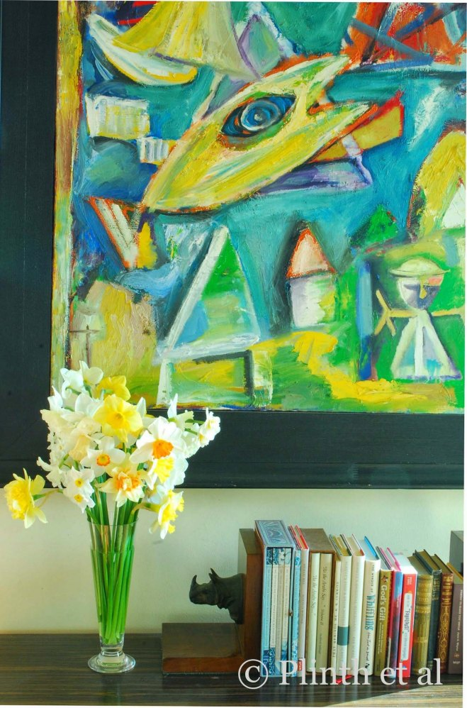 A bouquet of various daffodils connect with the bright yellows and blues of the abstract painting in a private home.
