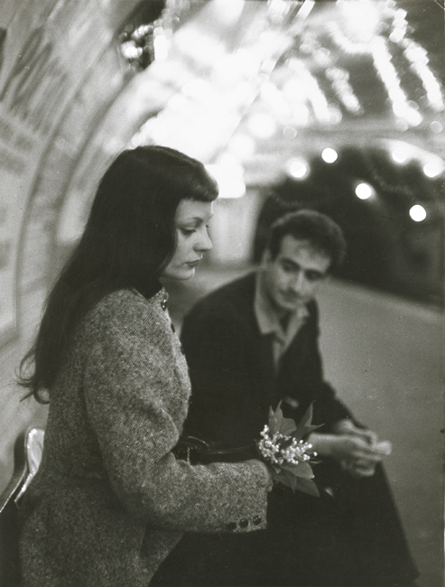 "Robert Doisneau's ""Le Muguet du Métro"" (Marc and Christiane Chevalier in the Paris Metro) - The woman averts her gaze away from the expectant man on the muguet, which appear remarkably fragile in the hard carapace of the Paris Metro. With his hands clasped and eyes downcast, the man seemingly awaits the woman's reaction as if apologetic for an unspoken wrongdoing."