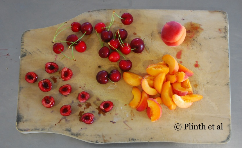Cherries and peaches are depitted and halved for clafoutis. Their vivid cheerful colors are retained in baking, making for a visually appealing pattern in the neutral hued clafoutis.