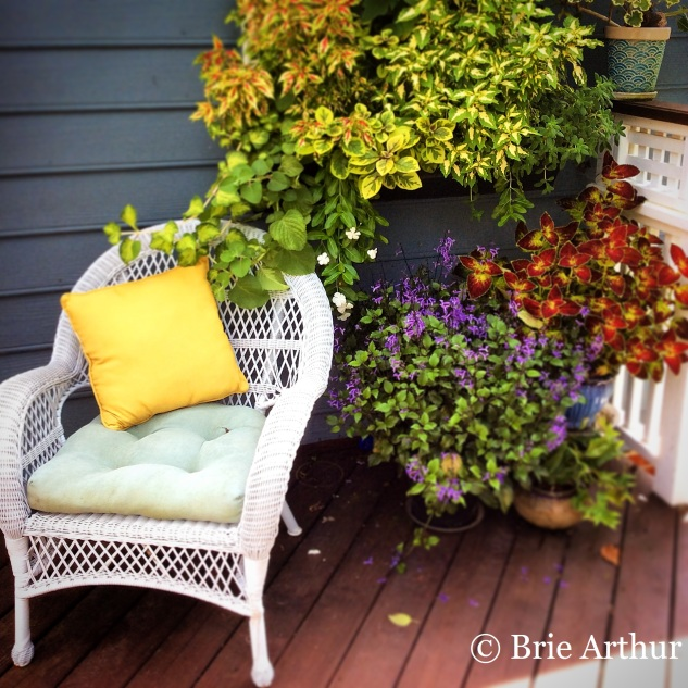 Colorful container plantings create an inviting backdrop for the porch lounge chair in Brie's garden.