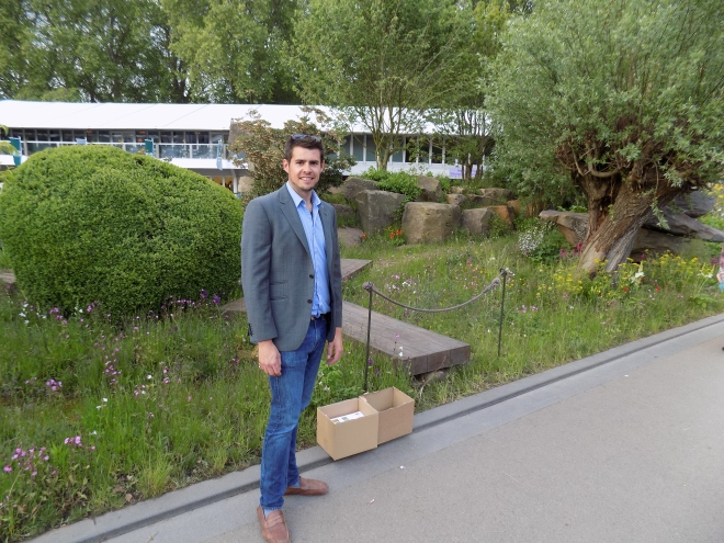 Looking dapper, Austin poses in front of a show garden at the 2015 RHS Chelsea Flower Show.